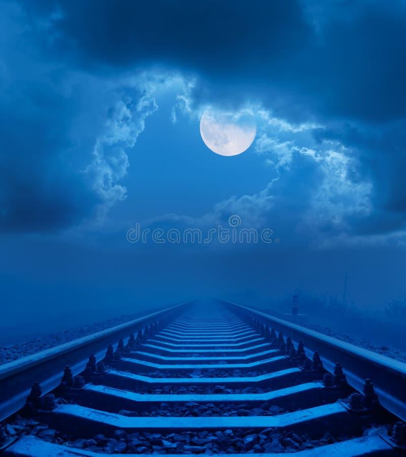 Volle maan in nachthemel met wolken over spoorweg royalty-vrije stock foto's