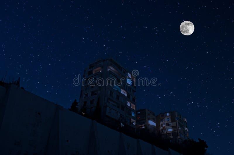 Volle maan over de stad bij nacht, Baku Azerbaijan Het grote volle maan glanzen helder over wolkenkrabbers royalty-vrije stock afbeelding