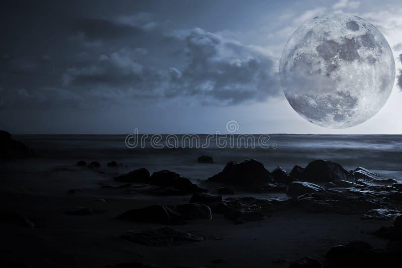Volle maan, overzees en gloeiende rotsen royalty-vrije stock foto