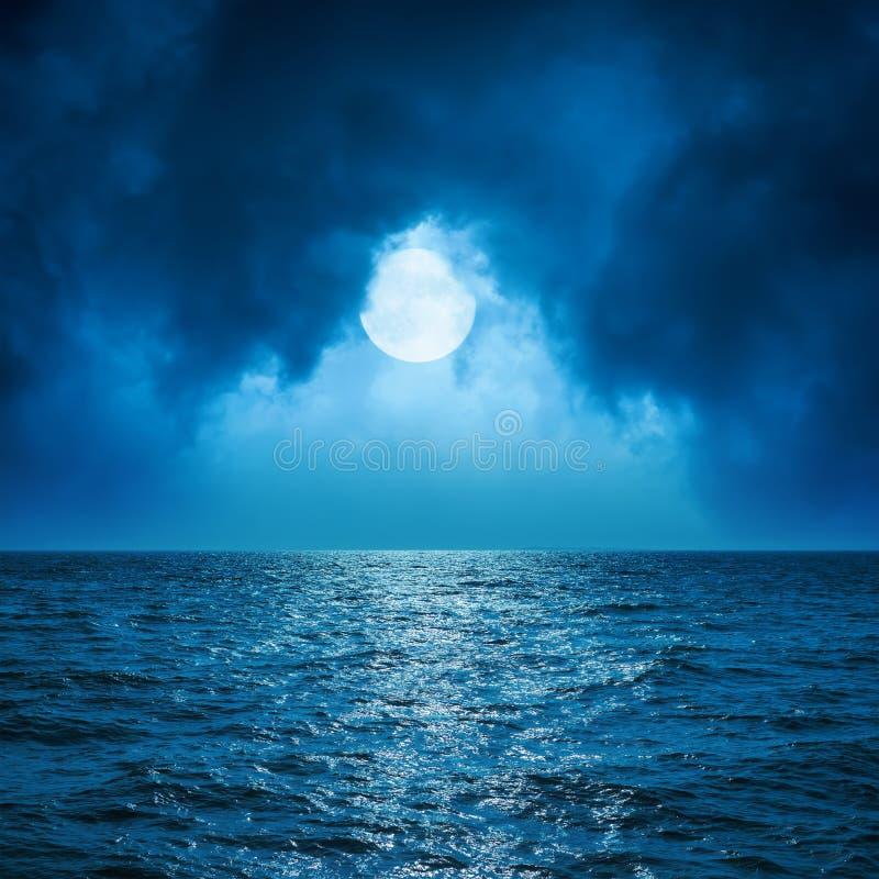 Volle maan in wolken over donkere overzees royalty-vrije stock afbeeldingen