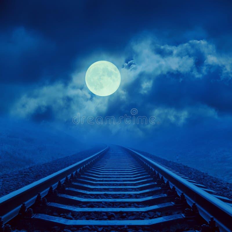 Volle maan in wolken over nachtspoorweg royalty-vrije stock fotografie
