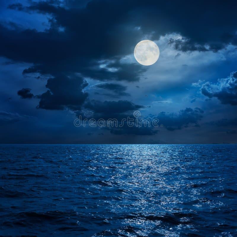 Volle maan in wolken over overzees stock afbeeldingen