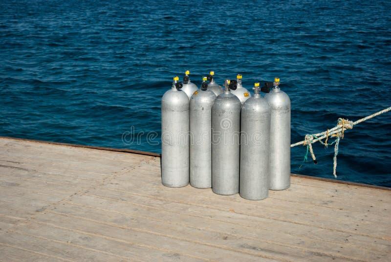 Volle Sauerstoffflaschen auf Pier Acht Zylinder mit Luft für das Tauchen acht Aluminiumzylinder auf Seedock stockbilder