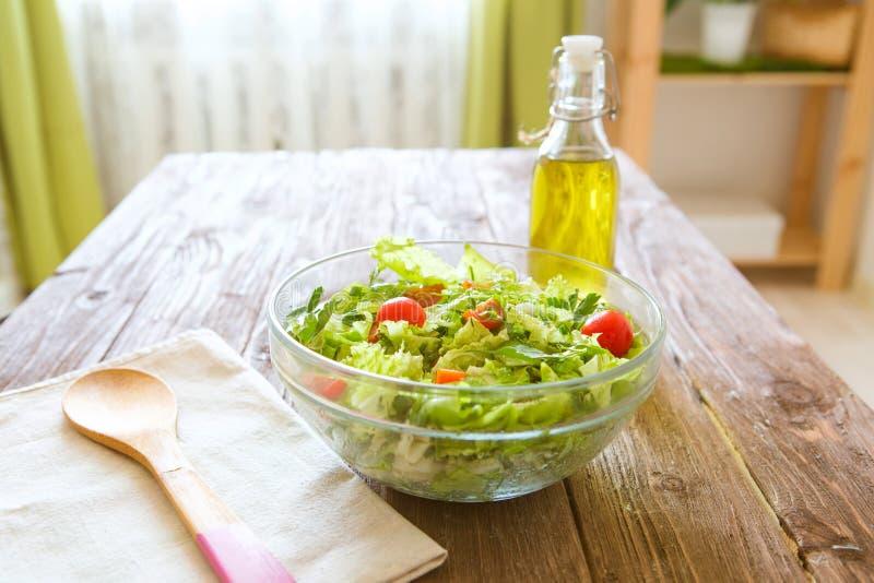 Volle Schüssel frischer grüner Salat auf einem Holztisch gegen an eine rustikale Küche Gesunder Lebensstil des Konzeptes und einf lizenzfreie stockfotos