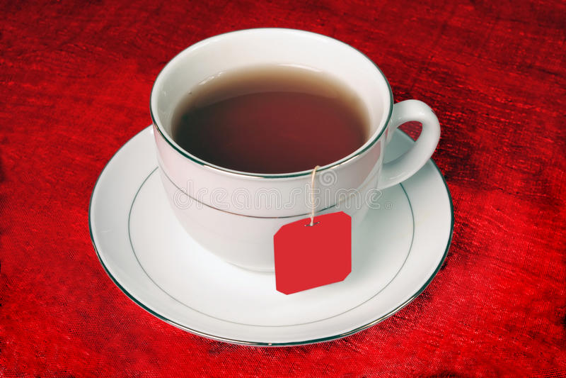 Volle Teeschale auf rotem Hintergrund lizenzfreie stockfotos