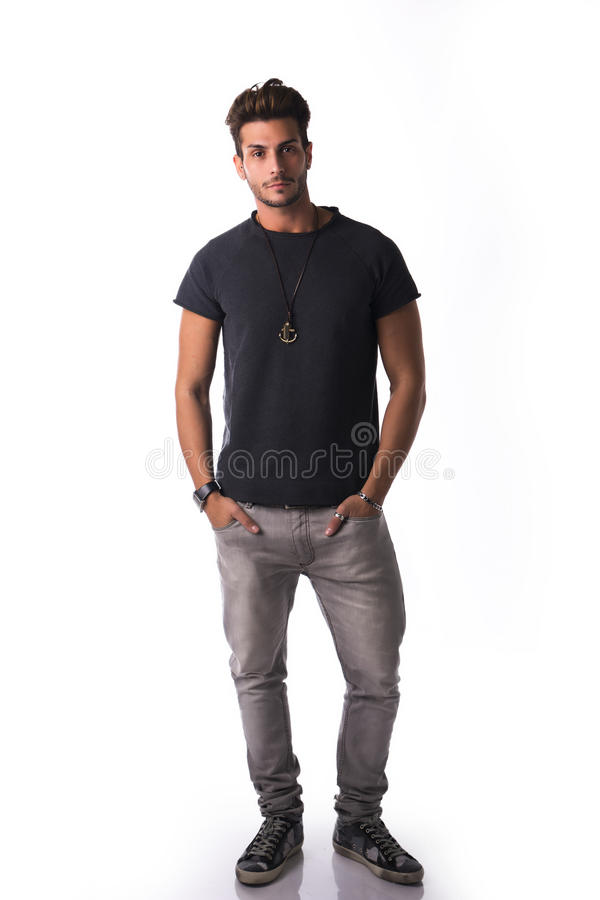 Volle Zahl des hübschen jungen Mannes, der in der zufälligen Kleidung überzeugt steht stockbild