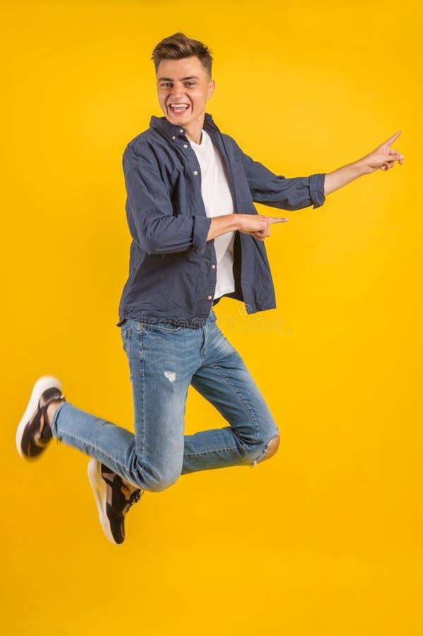 Volledig beeld van een opgewonden jongeman in een wit T-shirt die springt terwijl hij het succes viert stock fotografie