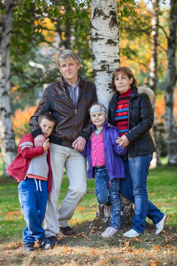 Volledig de lengteportret van de vier mensenfamilie in de herfstpark royalty-vrije stock foto