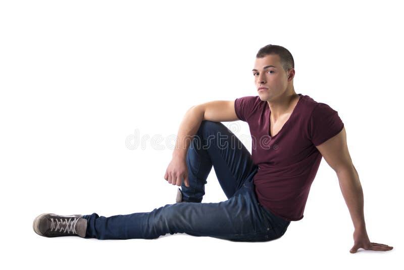 Volledig die lichaam van knappe jonge mensenzitting wordt geschoten op vloer stock afbeeldingen
