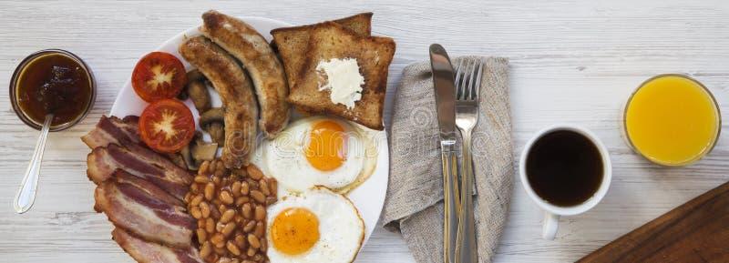 Volledig Engels ontbijt met gebraden eieren, worsten, bacon, bonen en toosts op witte houten achtergrond, hoogste mening Close-up royalty-vrije stock afbeelding