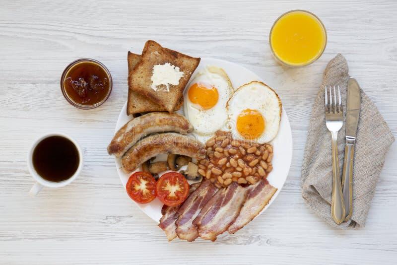 Volledig Engels Ontbijt op een wit om plaat met gebraden eieren, bacon, worsten, bonen en toosts op witte houten achtergrond, hoo royalty-vrije stock afbeelding