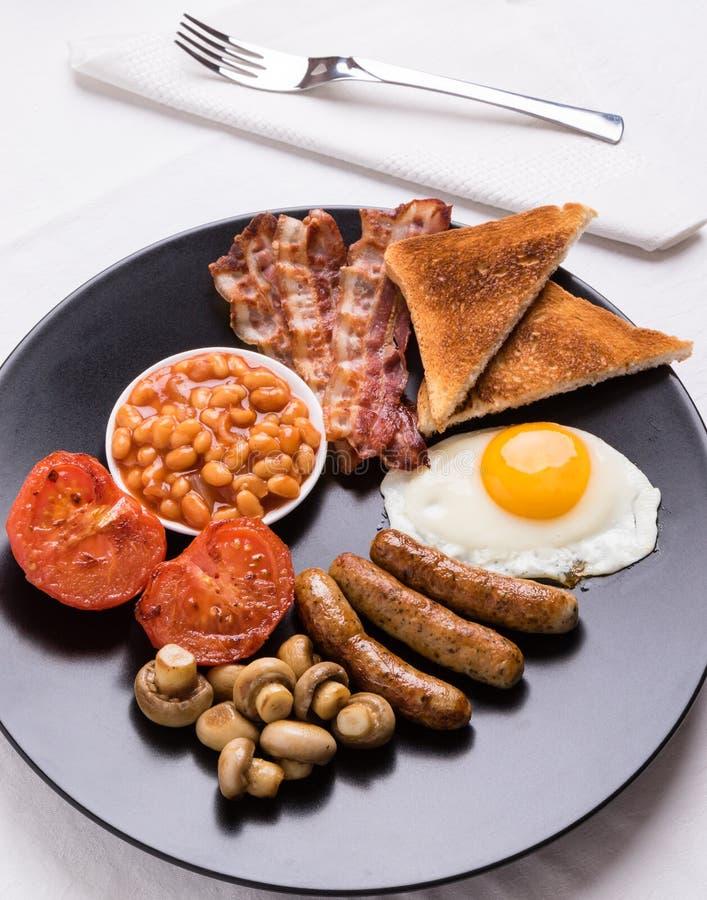 Volledig Engels ontbijt op zwarte plaat stock fotografie