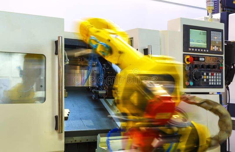 Volledig geautomatiseerde CNC die met de behandeling van robot in motieonduidelijk beeld machinaal bewerken stock afbeelding