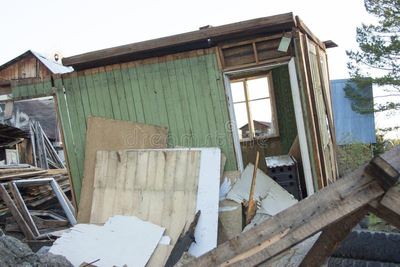 Volledig geruïneerd huis, gebroken vensters Huisvuil, banden, houten raad, stukken van triplex stock afbeelding