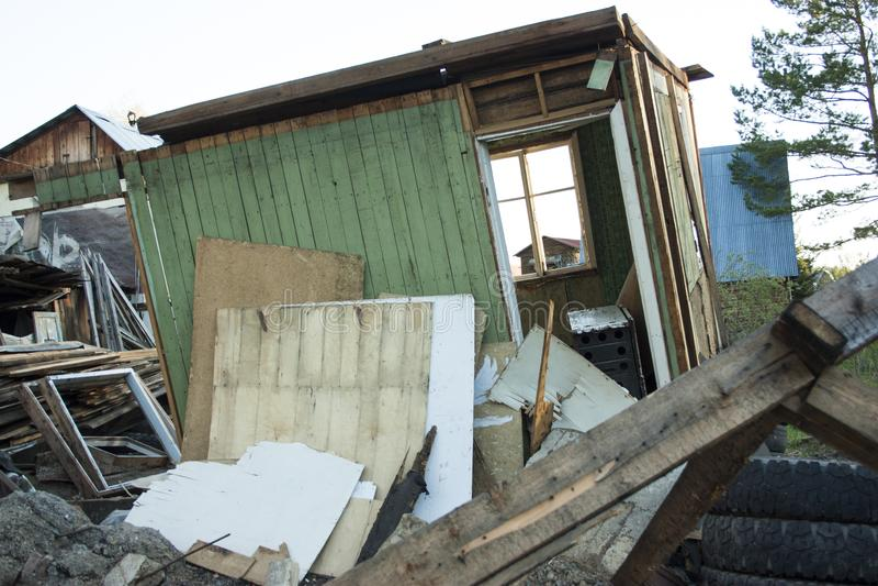 Volledig geruïneerd huis, gebroken vensters Rond verschillend huisvuil, banden, raad, stukken van triplex stock foto