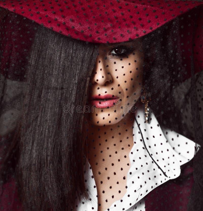 Volledig-gezichtsportret van geheimzinnig damebrunette in donkerrode hoed met haar neer sluier royalty-vrije stock afbeeldingen