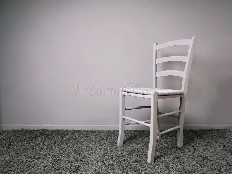 Volledig grijze ruimte met lege stoel en exemplaarruimte stock foto