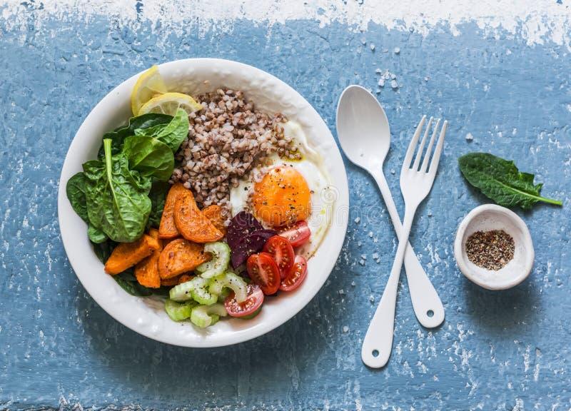 Volledig kom gezond voedsel - boekweit, gebakken bataten, spinazie, ei, bieten, selderie, tomaten Heerlijke dieetlunch op blauwe  royalty-vrije stock afbeeldingen