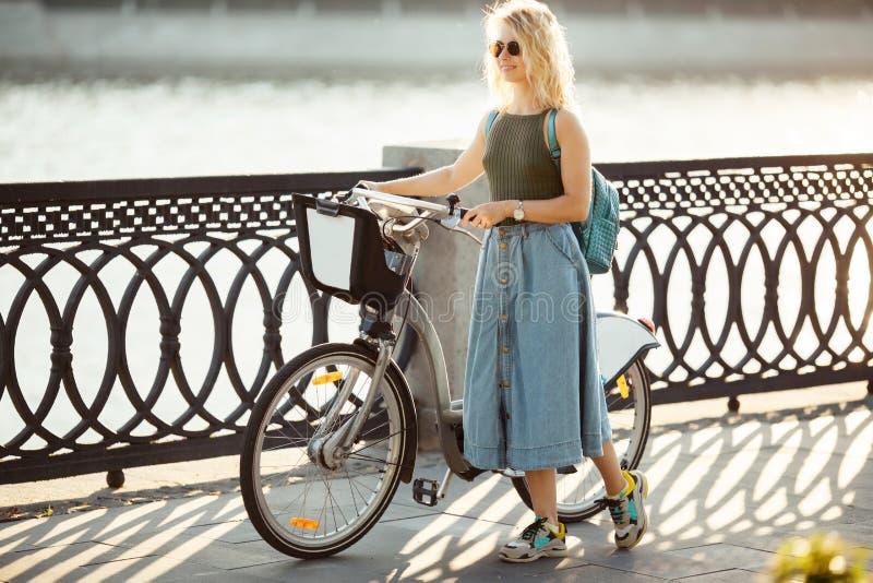 Volledig-lenght-hoogtepuntfoto van krullende blondevrouw die kant in denimrok bekijken die zich naast fiets op brug in stad bevin royalty-vrije stock afbeelding