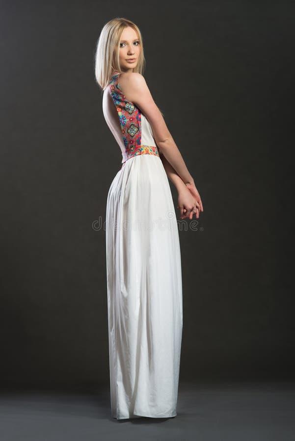 Volledig-lenght-hoogtepuntportret van bnondevrouw in witte lange kleding stock afbeeldingen