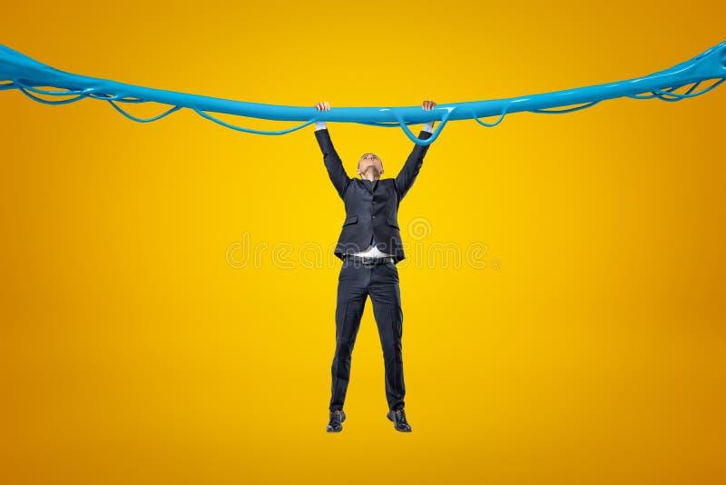 Volledig lengte vooraanzicht van zakenman het hangen het grijpen bij blauwe kleverige slijmdraad op amberachtergrond stock fotografie