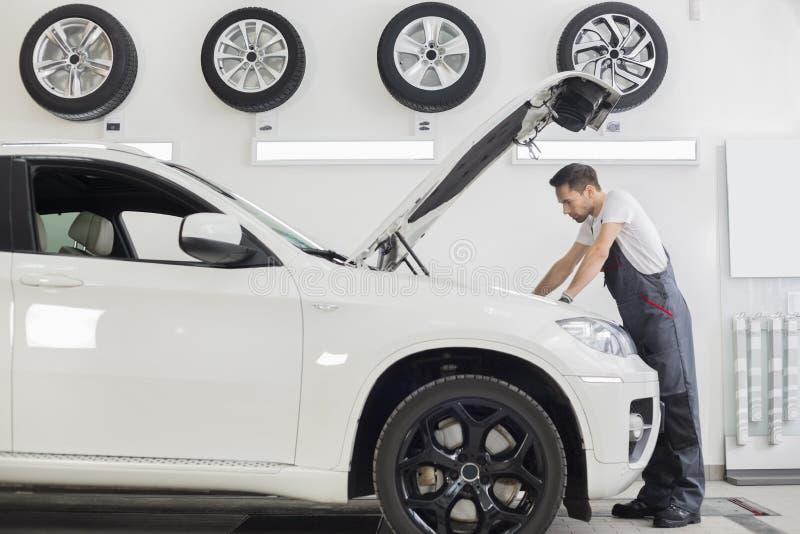 Volledig lengte zijaanzicht van mannelijke mechanische het onderzoeken motor van een auto in reparatiewerkplaats royalty-vrije stock afbeelding