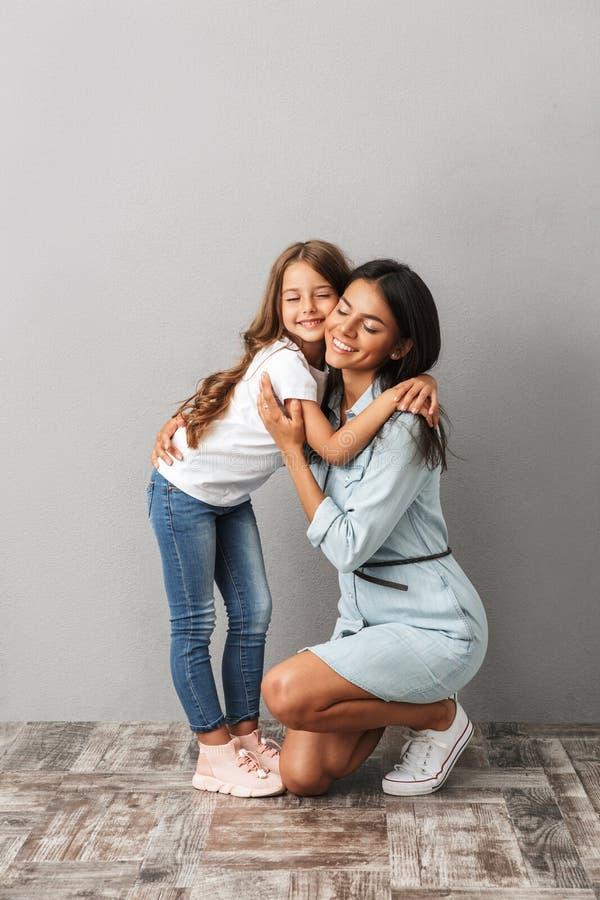 Volledig lengtebeeld van gelukkige vrouw met dochter het glimlachen en huggi royalty-vrije stock fotografie