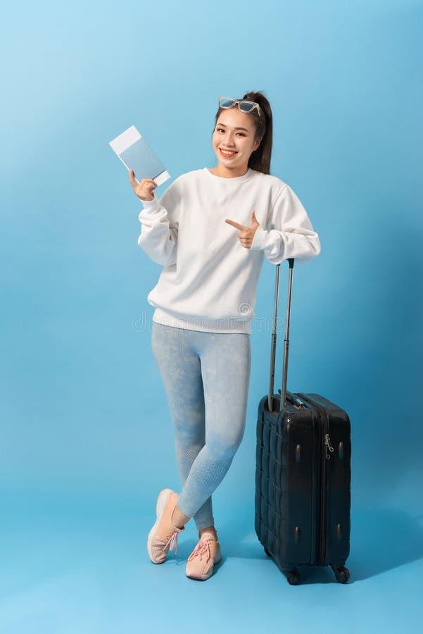 Volledig lengtebeeld van het Vrolijke vrouw dragen in toevallige kleding die met bagage en kaartjes over blauwe achtergrond voorb royalty-vrije stock fotografie
