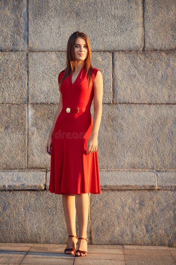 Volledig lengteportret van aantrekkelijke jonge vrouw in een rode kleding stock fotografie