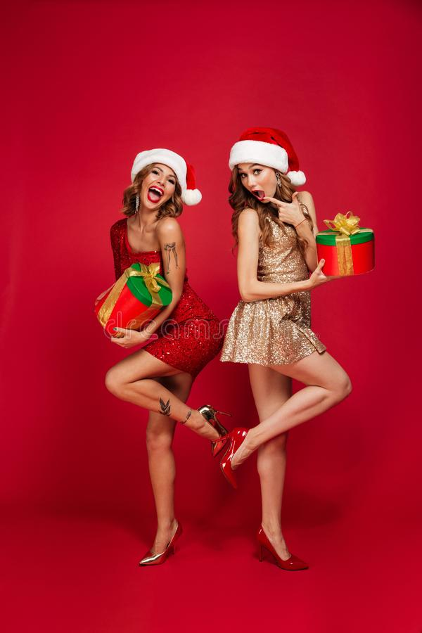 Volledig lengteportret van blije jonge vrouwen in Kerstmishoeden stock foto