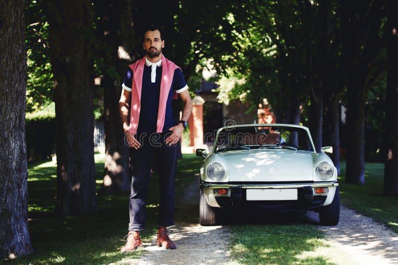 Volledig lengteportret van de knappe donkerbruine mens die zich tegen luxecabriolet auto bij platteland bevinden stock fotografie