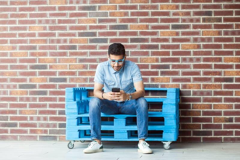 Volledig lengteportret van de succesvolle knappe jonge gebaarde mens in toevallige stijl, oogglazen die op blauwe houten pallet,  stock foto