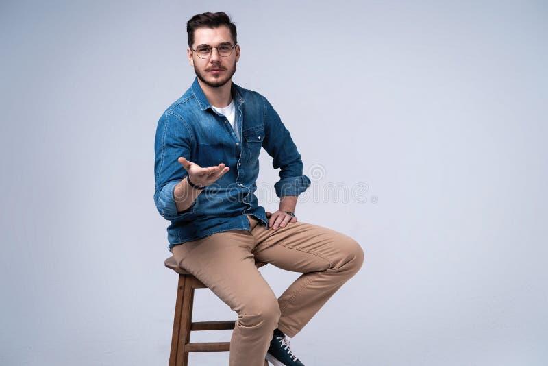 Volledig lengteportret van een aantrekkelijke jonge mens in de zitting van het jeansoverhemd op de stoel over grijze achtergrond royalty-vrije stock foto's