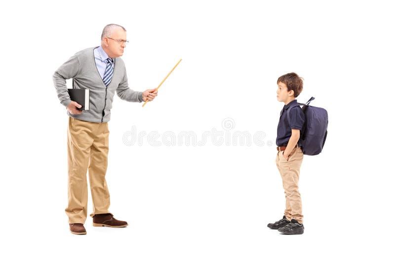 Volledig lengteportret van een boze leraar die bij een schooljongen schreeuwen stock foto's