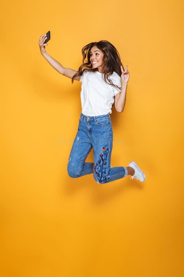 Volledig lengteportret van een gelukkig meisje met het lange donkere haar springen stock afbeeldingen