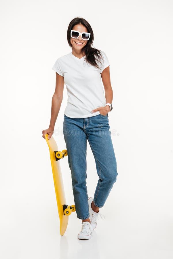 Volledig lengteportret van een gelukkige donkerbruine vrouw in zonnebril stock afbeelding