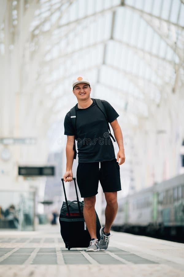 Volledig lengteportret van een gelukkige jonge mens die met koffer bij station lopen reis concept stock foto