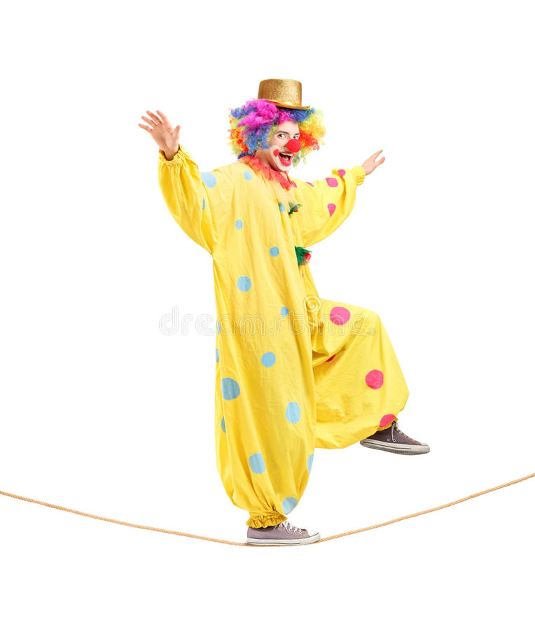 Volledig lengteportret van een gelukkige mannelijke clown die op een kabel lopen stock afbeelding