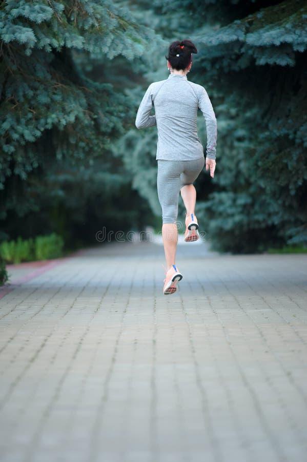 Volledig lengteportret van een geschiktheidsvrouw die bij het park lopen bac stock foto