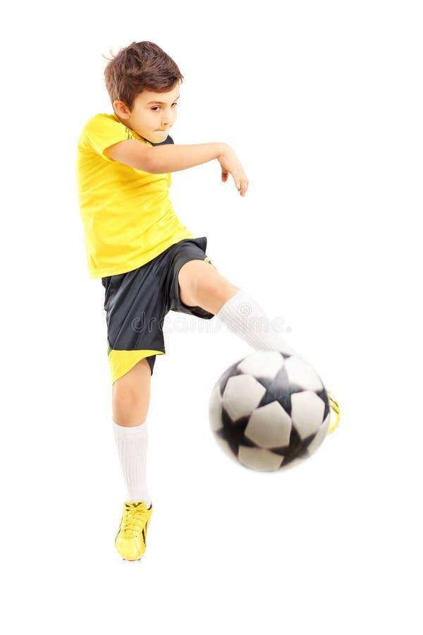 Volledig lengteportret van een jong geitje in sportkleding die een voetbalbedelaars schieten stock fotografie
