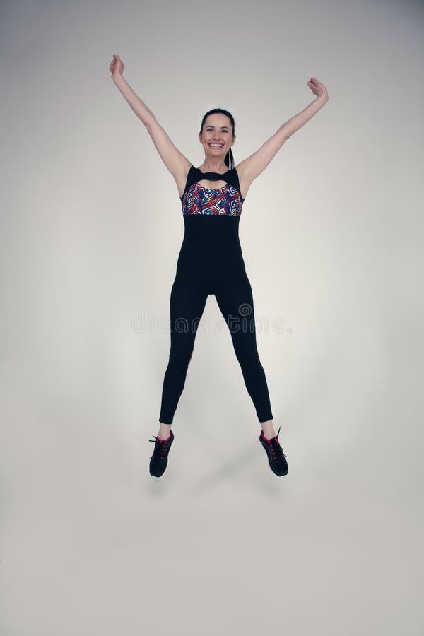 Volledig lengteportret van een jonge geschiktheidsvrouw in en sportkleding die ge?soleerd over grijze achtergrond stellen springe royalty-vrije stock afbeelding