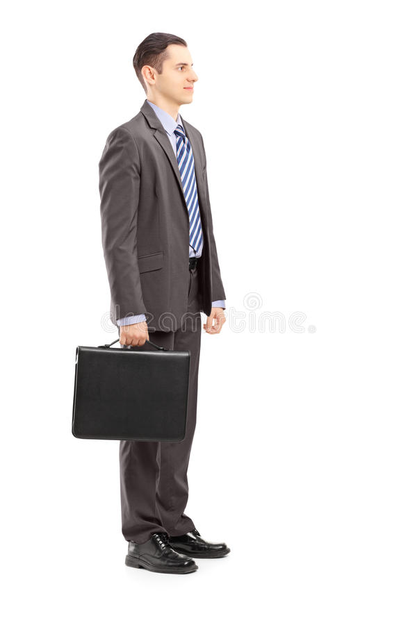 Volledig lengteportret van een jonge zakenman met aktentastribune stock fotografie