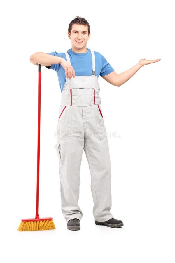 Volledig lengteportret van een mannelijke reinigingsmachine met bezem het gesturing