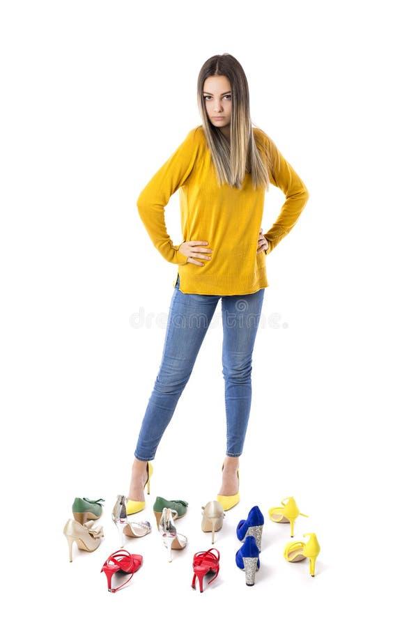 Volledig lengteportret van een modieuze jonge vrouw met vele schoenen op de vloer tegen wit Het concept van het consumentisme stock afbeelding