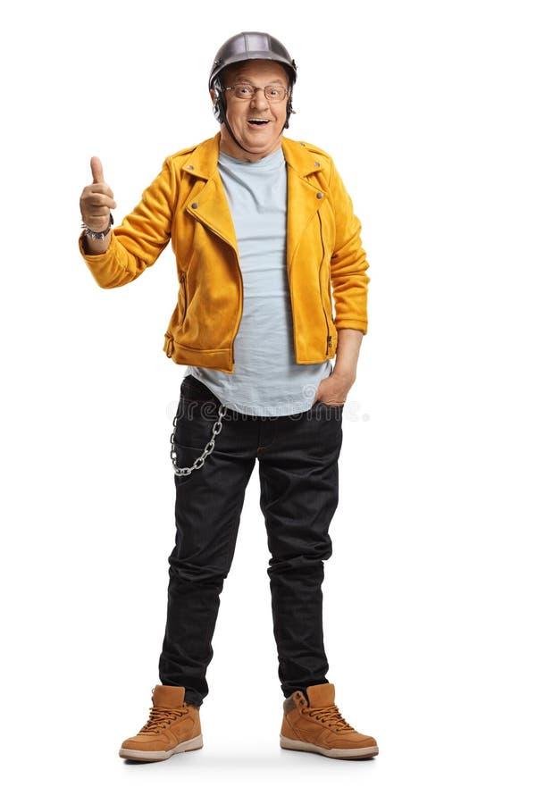 Volledig lengteportret van een rijpe motorrijder in een gele leren jas met duim omhoog stock foto