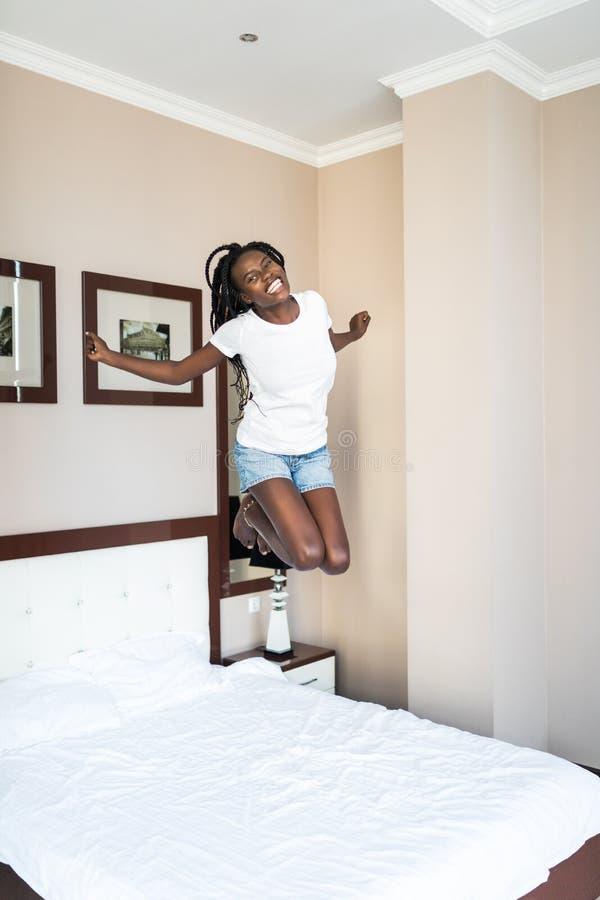 Volledig lengteportret van een vrolijke afro Amerikaanse vrouw in oortelefoons die en op bed binnen zingen springen royalty-vrije stock foto