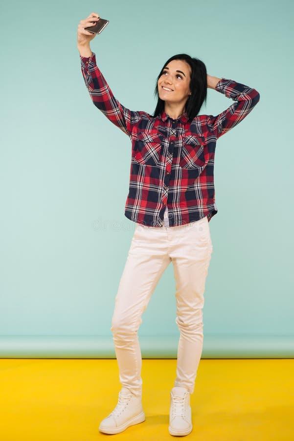 Volledig lengteportret van een vrolijke glimlachende vrouw in plaidoverhemd nemen selfie geïsoleerd op een achtergrond royalty-vrije stock afbeelding