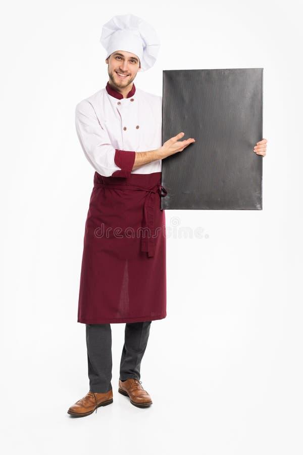 Volledig lengteportret van een vrolijke mannelijke chef-kokkok in eenvormige holdings lege die raad op een witte achtergrond word royalty-vrije stock fotografie