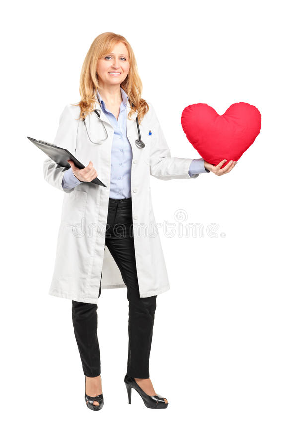 Volledig lengteportret van een vrouwelijke arts die een rood hart houden stock foto's