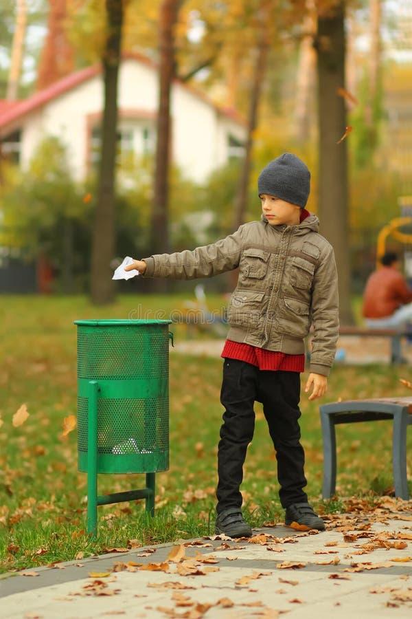 Volledig lengteportret van een zes éénjarigenjongen die document aan de afvalbak/vuilnisbak in het park werpen royalty-vrije stock foto